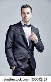 Young man wearing bow tie and black suit isolated over gray