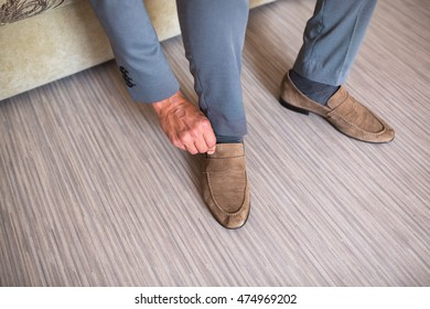 Young man wearing brown chamois shoes with suite and grey pants. Sitting hipster guy with old elegant shoes. Main focus on laces