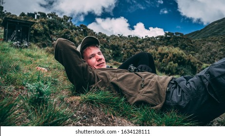 Young man wearing a cap resting in the jungle / hills in Tanzania Africa