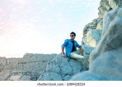 Young man wearing casual clothes and sunglasses, sitting on some rocks near the seashore. Young man watching the sunset on the beach. Man modeling and showing his sexiest side.