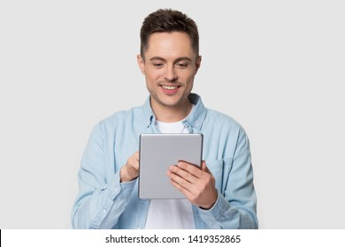 Young man wearing casual clothes jeans shirt holds modern gadget use tablet computer pose isolated on white grey studio background, wireless tech usage internet media and online communication concept