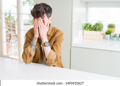 Young man wearing casual jacket sitting on white table with sad expression covering face with hands while crying. Depression concept.
