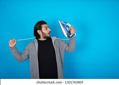 Young man wearing a casual outfit, chocking himself with an iron wire, standing on a blue background