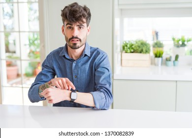 Young man wearing casual shirt sitting on white table In hurry pointing to watch time, impatience, upset and angry for deadline delay