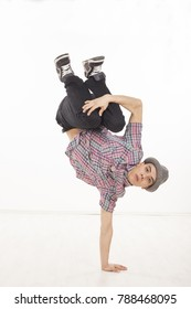 Young man wearing casual shirt dancing sitting on one hand, performing breakdance moves on wood floor upside down, with legs up. Vertical image in studio on white background.
