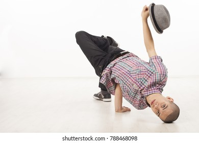 Young man wearing casual shirt dancing sitting on one hand, performing breakdance moves upside down, with head on the floor and hat up. Horizontal image in studio on white background.