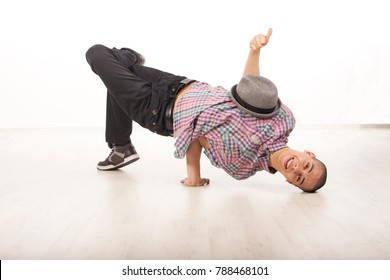 Young man wearing casual shirt dancing sitting on one hand and his head, performing breakdance moves on wood floor upside down. Horizontal image in studio on white background.