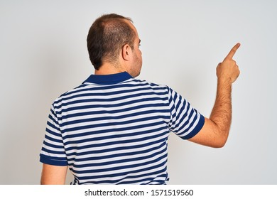 Young man wearing casual striped polo standing over isolated white background Posing backwards pointing ahead with finger hand
