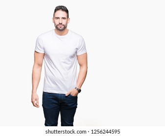 Young man wearing casual white t-shirt over isolated background Relaxed with serious expression on face. Simple and natural looking at the camera.