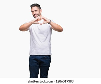 Young man wearing casual white t-shirt over isolated background smiling in love showing heart symbol and shape with hands. Romantic concept.
