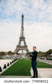 A young man wearing a dark blue jacket is standing on the background of the Eiffel Tower. Sunny weather is autumn