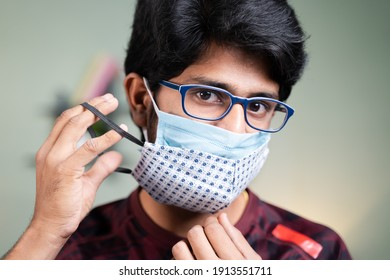 Young man wearing double or two face mask to protect from coronavirus or covid-19 outbreak - concept of safety, healthcare, medical and hygiene.