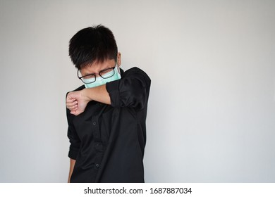 Young man wearing face hygienic mask.  Protection global covid-19 virus pandemic. He use his arm protect when he have fever illness, cough, sneeze.