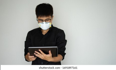 The young man wearing face hygienic mask, N95.  Protect the outbreak global covid-19 virus pandemic. He have chest pain and need medicine. Use labtop checking news.