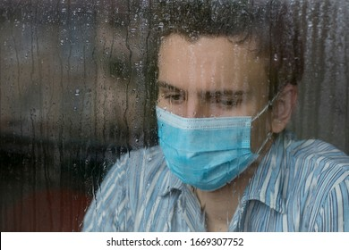 Young man wearing a face mask, sick with COVID-19 and quaranteened, looking outside the hospital window