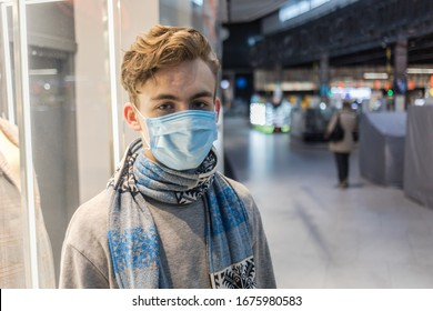 Young man wearing face mask, protection against coronavirus. Covid-19 person. Walking in big shopping mall, world amid corona virus situation