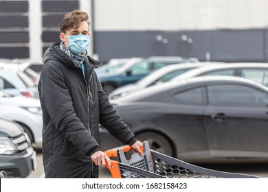 Young man wearing face mask, protection against coronavirus. Covid-19 person. Standing on big parking near supermarket, world amid corona virus situation