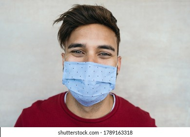 Young man wearing face mask portrait - Latin boy using protective facemask for preventing spread of corona virus - Health care and youth millennial people concept