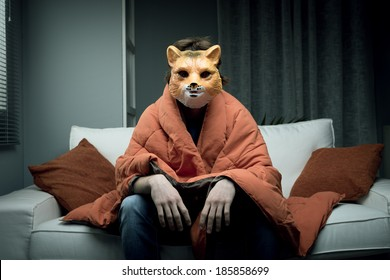 Young man wearing a fox mask sitting on sofa covered with a blanket.