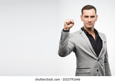 A young man wearing a gray suit shows a sign fist up. Copy space. Isolated on white. Advertising, fashion and commercial Design,