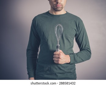 A young man wearing a green top is holding a balloon whisk