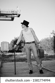 Young man, wearing grey pants, white top and black classic hat, holding old suitcase, leaning on cane. Black and white picture of creative man on abandoned construction site area. Art-house.