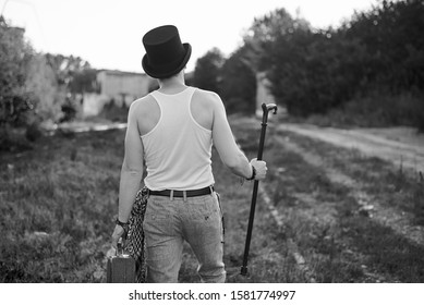 Young man, wearing grey pants, white top and black classic hat, holding old suitcase,and cane, walking away from camera. Black white picture of creative man on abandoned construction site. Art-house