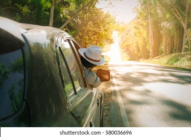 Young man wearing hat  from driver seat through opened window. Vacation and travel concepts.