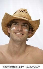 young man wearing hat with sunblock on cheeks