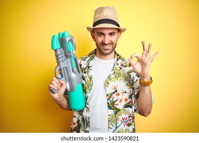 Young man wearing hawaiian flowers shirt holding water gun over yellow isolated background doing ok sign with fingers, excellent symbol