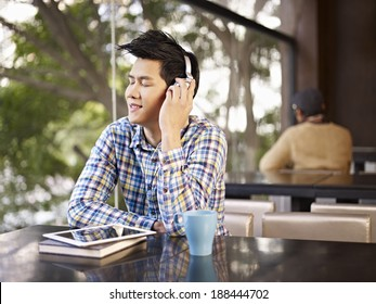 young man wearing headphone enjoying music in cafe