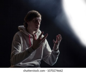 young man wearing hoody making gesture. low key portrait.concept of psychic or magician or esoteric