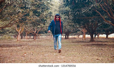 Young man wearing jacket walking around a park unique photo