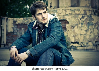 Young man wearing jeans clothes sits on the ground in front of the cracked ruined wall.