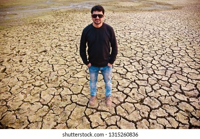 Young man wearing jeans and shoes standing on a cracked soil surface
