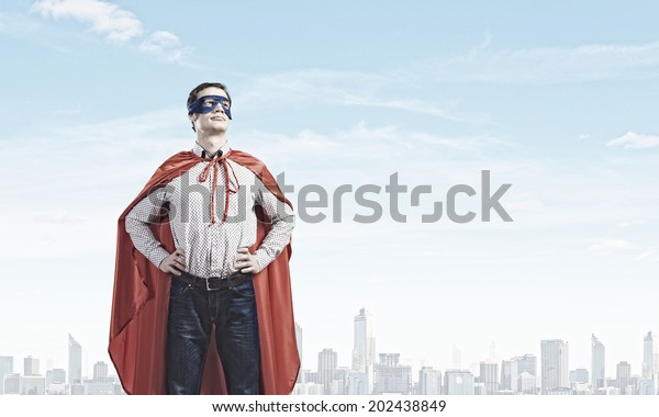 Young man wearing mask and cape