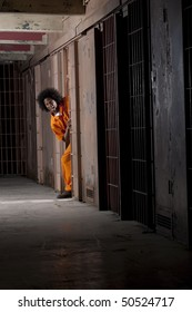 A young man wearing an orange prison jumpsuit makes a face as he peeks out from within his prison cell. Vertical shot.