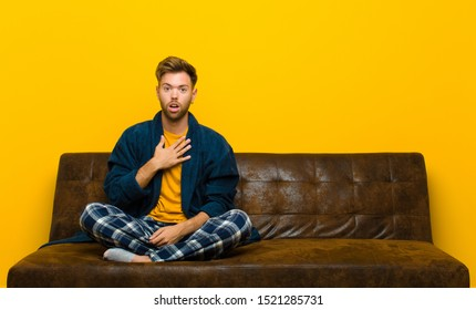 young man wearing pajamas feeling shocked, astonished and surprised, with hand on chest and open mouth, saying who, me? . sitting on a sofa