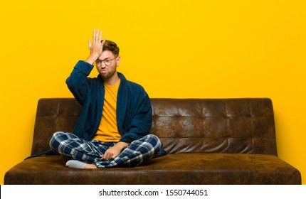 young man wearing pajamas raising palm to forehead thinking oops, after making a stupid mistake or remembering, feeling dumb . sitting on a sofa