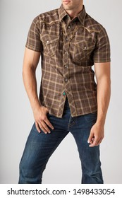 Young man wearing plaid western wear shirt and denim jeans. Men's trendy casual clothing fashions styles.
