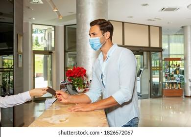 Joven con protección de mascarilla en recepción del hotel