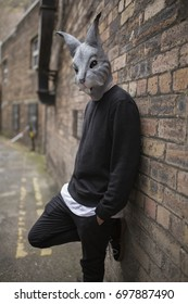 young man wearing a rabbit mask leaning on to a brick wall wearing black dark clothes