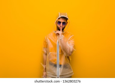 Young man wearing a rain coat keeping a secret or asking for silence
