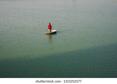 Young man wearing red jacket standing on a concrete boat around a lake