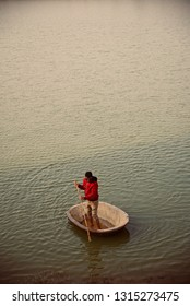 Young man wearing red jacket paddling on a floating concrete boat