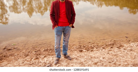 Young man wearing red shirt standing around a lake shore area