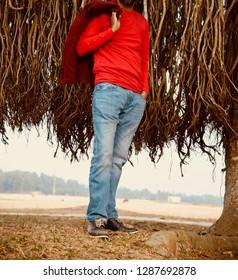 Young man wearing red t shirt and blue jeans standing in a place