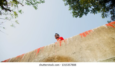 Young man wearing red t shirt sitting in a place with sky background photo