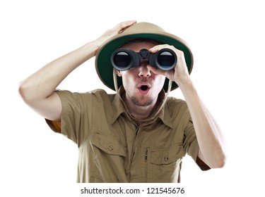 Young man wearing safari shirt and pith helmet looking through binoculars with a surprised expression, isolated on white