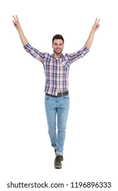 young man wearing a shirt with plaids walking on white background and celebrating with hands in the air, full length picture